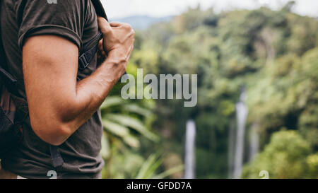 Close up shot of young man hand with backpack standing in nature near a waterfall. Man hiking near waterfall in - Stock Photo