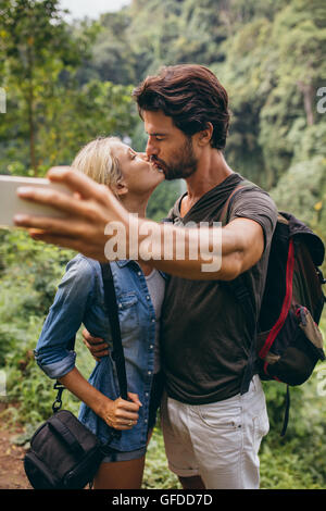 Loving young couple kissing and taking self portrait with their cell phone. Couple in love taking self picture in - Stock Photo