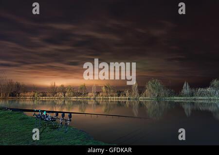Night Fishing, Carp Rods, Cloudscape reflection on lake - Stock Photo