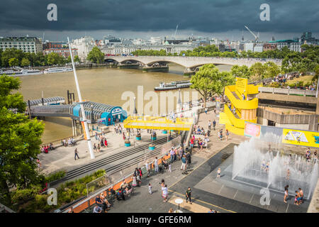 Children playing in the Appearing Rooms fountains on the Southbank, London, UK - Stock Photo