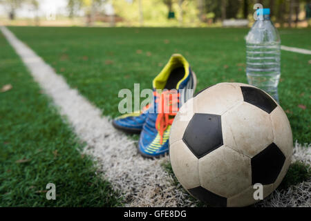Football cleat and fresh water after the match on the field - Stock Photo