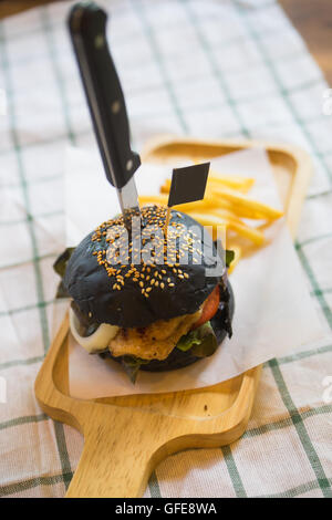 Selective focus Black burger with French fries - Stock Photo