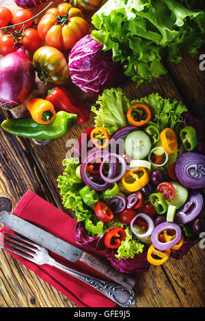 Spring salad with fresh juicy vegetables on a rustic wooden table. - Stock Photo