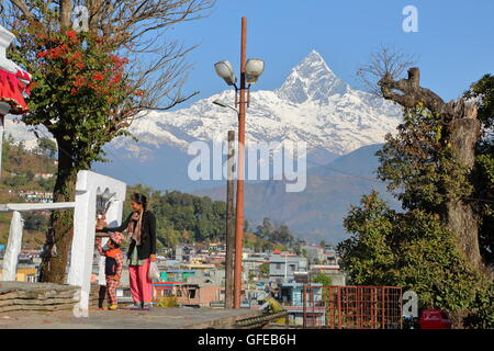 A Nepalese woman with her son ringing a bell at Bindhya Basini Temple in Pokhara, Nepal, Himalaya mountains - Stock Photo
