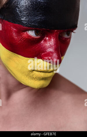 Soccer fan with german strip flag painted over face - Stock Photo