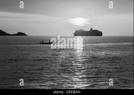 Dramatic sea and transport boat with sunset and over light the sun in twilight black and white tone - Stock Photo