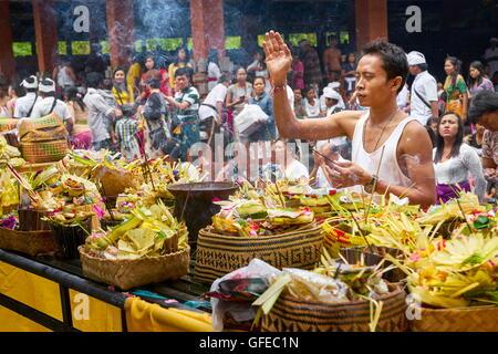 Man praying in Pura Tirta Empul Temple, Bali, Indonesia - Stock Photo