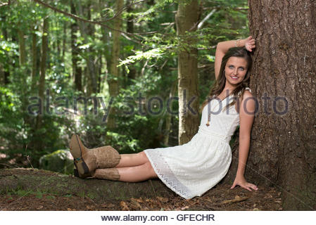 Beautiful young Caucasian woman wearing a white dress sits in the forest next to a tree - Stock Photo