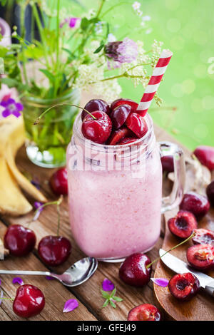 Fresh homemade healthy berry smoothie in mason jar on window background - Stock Photo