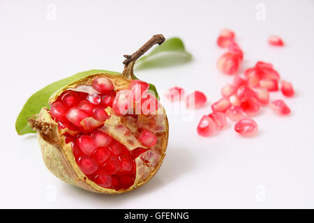 Open Pomegranate with seeds on white background - Stock Photo