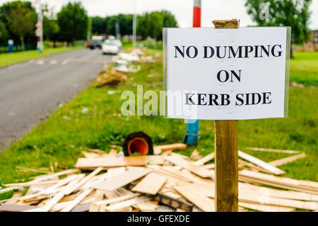 A sign on a grass verge warning people not to dump rubbish on the kerb side, with a lot of discarded wood, rubbish - Stock Photo