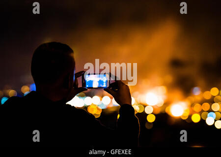 Belfast, Northern Ireland. 12th July 2016 - A man uses his mobile phone to take a photograph of loyalist bonfires - Stock Photo