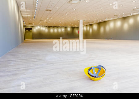Yellow safety helmet is placed upside down on the floor of a large showroom in a modern business centre with ceiling - Stock Photo