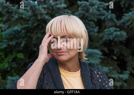 Elderly woman is having a headache and touching her head with her right hand - Stock Photo