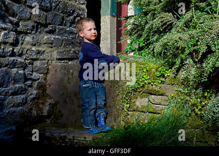 Two year old boy leaning on a wall - Stock Photo