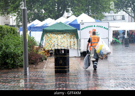 A council worker clears away bags of rubbish during a sudden summer rain storm in a busy city centre area - Stock Photo