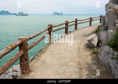 Empty path with wooden fence on a cliff facing the open sea with small islands in the distance - Stock Photo