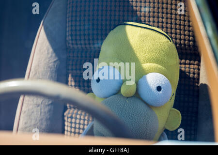 Homer Simpson soft toy doll behind the wheel of a car