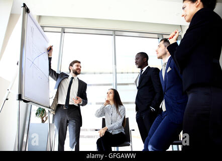Cheerful businessman discussing new business project with the members of his team - Stock Photo