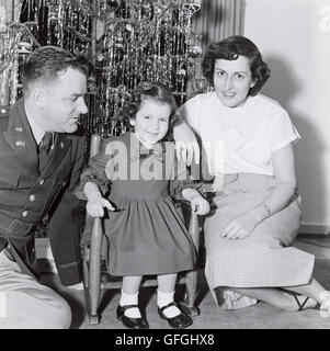 Vintage 1950's Christmas Photograph, Military Officer with Wife and Small Daughter in Front of Christmas Tree - Stock Photo