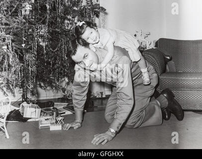 Vintage 1950's Christmas Photograph, Military Officer Small Daughter in Front of Christmas Tree - Stock Photo