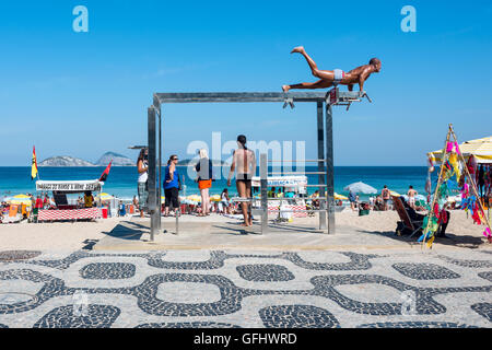 Rio de Janeiro, Brazil - July 24, 2016: Young man at one of the many outdoor fitness stations on Ipanema Beach - Stock Photo