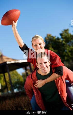 Series of a group of friends playing football in the park on an Autumn day. - Stock Photo