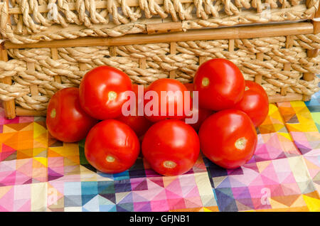 Tomatoes stacked against a woven basket - Stock Photo