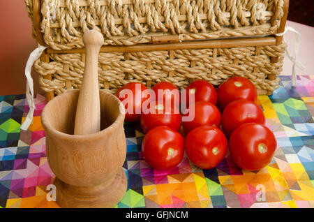 Tomatoes stacked against a woven basket with wooden mortar and pestle - Stock Photo