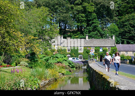 View along the trout farm garden and River Coln towards The Swan Hotel with tourists walking along the pavement, - Stock Photo