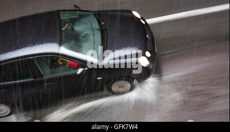Rainy day in the city: A driving car, with a red umbrella on the front seat, in the city street, hit by the heavy - Stock Photo