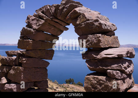 Taquile Island, Peru: A historic stone arch with view over Lake Titicaca - Stock Photo