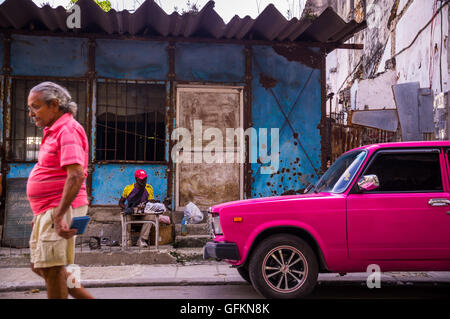 Havana, Cuba on December 23, 2015: A man walks down a street in Centro Habana with his shirt matching the color - Stock Photo