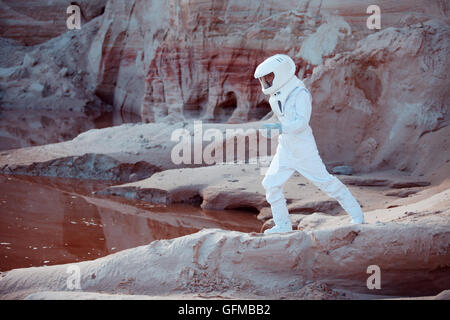 futuristic astronaut on another planet, sandy red planet ...