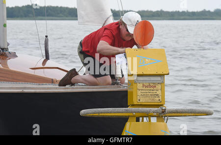 Steinhude, Germany. 27th July, 2016. Reinhard Starke of the sailing club Garbsen emptying a mail buoy that is anchored - Stock Photo