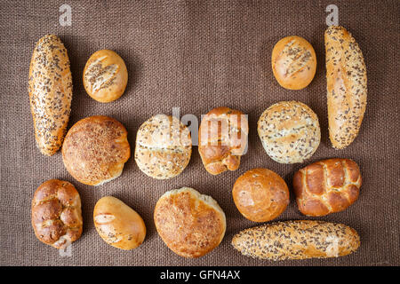 Different sorts of wholemeal breads and rolls on brown background - Stock Photo