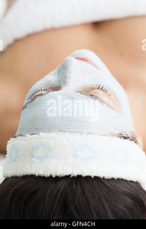 Facial mask application on young female patient - Stock Photo