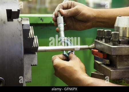 Man using a micrometer to measure a rod diameter - Stock Photo