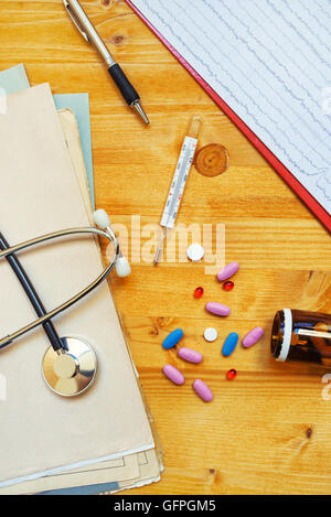Colorful medical tablets and pills scattered on doctor's office desk, top view - Stock Photo