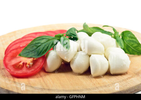 Mozzarella and sliced tomatoes with basil leaves - Stock Photo