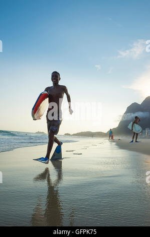 RIO DE JANEIRO - MARCH 8, 2016: Bodyboarders walk on São Conrado Beach under a sunset silhouette of the iconic Pedra - Stock Photo