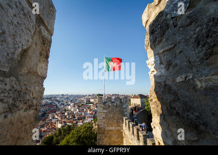 A Portuguese flag blowing in the wind, seen through an opening in castle walls - Stock Photo