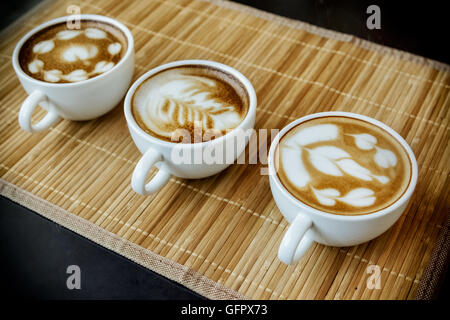 Three cups of cafe' latte with three shapes of latte art - Stock Photo