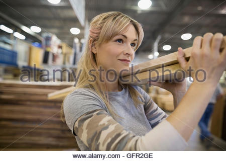 Confident woman carrying wood planks in home improvement store - Stock Photo