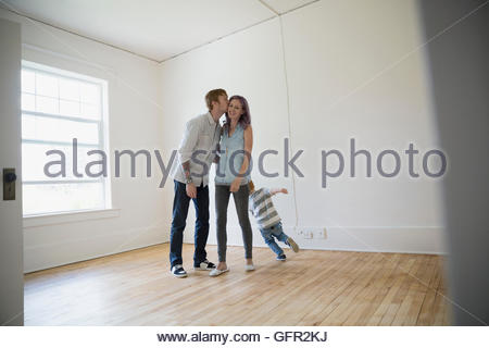 Young family kissing in empty new house - Stock Photo