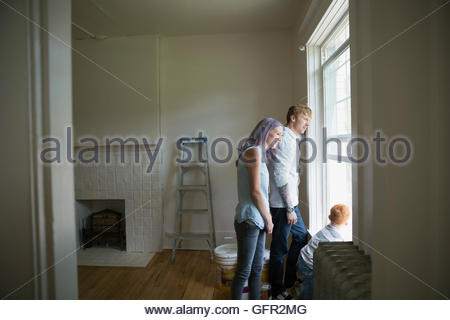 Young family looking out window in new house - Stock Photo