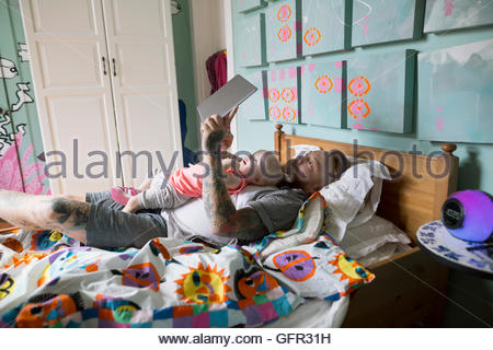Father and daughter laying in bed reading digital tablet - Stock Photo