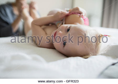 Close up portrait smiling baby girl laying on bed with doll - Stock Photo