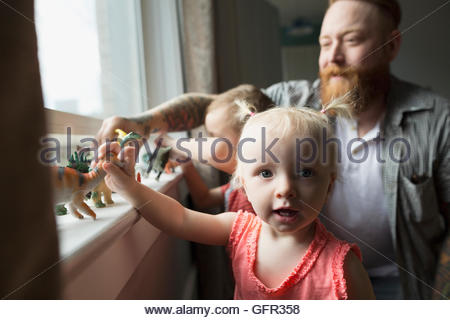 Portrait daughter and father playing with toy dinosaurs at windowsill - Stock Photo