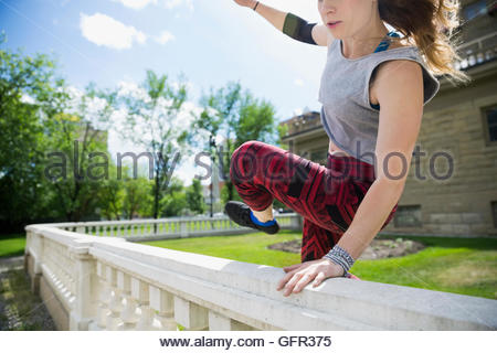 Young woman doing parkour jumping over railing - Stock Photo